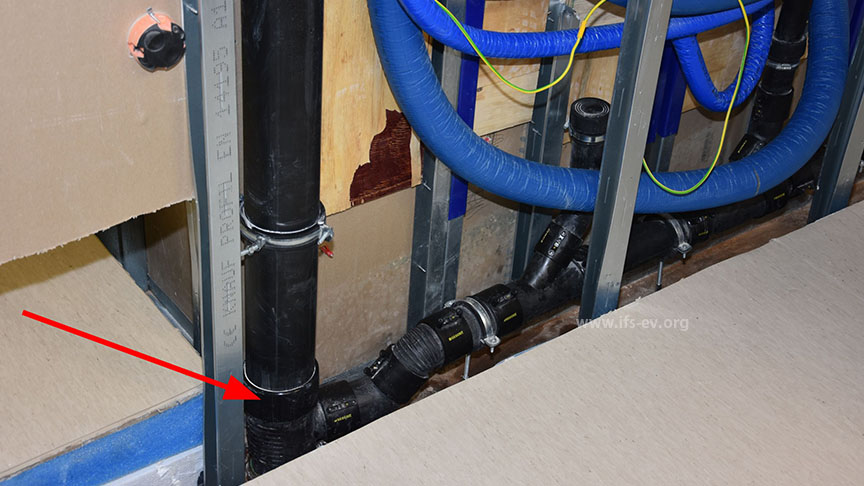 Die undichte Elektroschweißmuffe ist zwischen dem Fallrohr und einem Abzweig installiert (Pfeil).