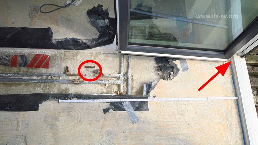 Die Schadenstelle (Markierung) liegt circa einen Meter vor der Balkontür (Pfeil).