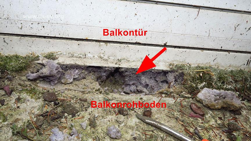 Der Spaltbereich zwischen Balkontür und Balkonrohboden ist lediglich mit Bauschaum ausgefüllt worden (Pfeil).