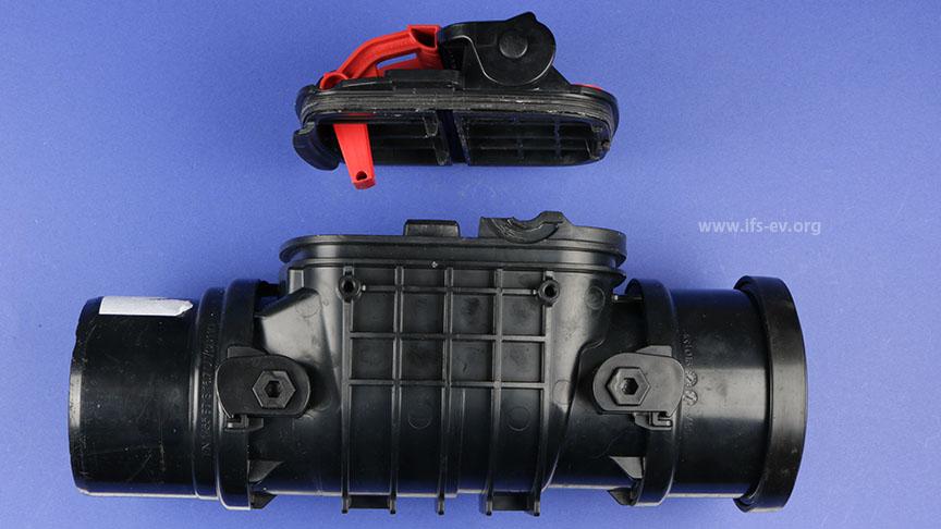 Die Rückstausicherung aus dem zweiten unten geschilderten Fall besteht aus einem Grundkörper mit zwei eingesetzten Klappen und einem Deckel mit Notverschluss-Hebel (rot).